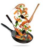 Φρέσκα θαλασσινά και λαχανικά που πετούν σε ένα τηγάνι στο άσπρο backgro στοκ εικόνα