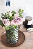 Φρέσκα θερινά τριαντάφυλλα χρώματος κρητιδογραφιών πορφυρά, μωβ στο βάζο στο CL δίσκων Στοκ Φωτογραφίες