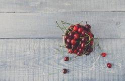 Φρέσκα κεράσια στο μπλε αγροτικό ξύλο Στοκ εικόνα με δικαίωμα ελεύθερης χρήσης