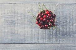 Φρέσκα κεράσια στο μπλε αγροτικό ξύλο Στοκ Εικόνες