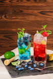 Φρέσκα κοκτέιλ με τη μέντα, τον ασβέστη, τον πάγο, τα μούρα και το carambola στο ξύλινο υπόβαθρο Αναζωογονώντας θερινά ποτά διάστ Στοκ Εικόνες