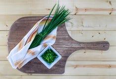 Φρέσκα κρεμμύδια στον ξύλινο πίνακα με την εκλεκτής ποιότητας πετσέτα Στοκ εικόνα με δικαίωμα ελεύθερης χρήσης