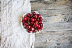 Φρέσκα κόκκινα κεράσια σε ένα πιάτο, σε ένα υπόβαθρο του πράσινου κήπου, Στοκ Φωτογραφία