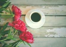 Φρέσκα κόκκινα λουλούδια peonies και φλυτζάνι καφέ Στοκ εικόνες με δικαίωμα ελεύθερης χρήσης