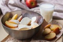 Φρέσκα κόκκινα μήλα που ψεκάζονται με το αλεύρι σε ένα μοντέρνο πιάτο σιδήρου που βρίσκεται σε μια άσπρη στρωματοειδή φλέβα παραθ Στοκ Φωτογραφία