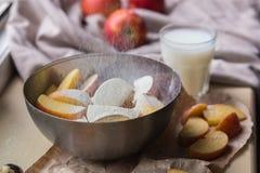 Φρέσκα κόκκινα μήλα που ψεκάζονται με το αλεύρι σε ένα μοντέρνο πιάτο σιδήρου που βρίσκεται σε μια άσπρη στρωματοειδή φλέβα παραθ Στοκ Εικόνες