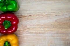 Φρέσκα κόκκινα πράσινα κίτρινα γλυκά πιπέρια στο ξύλινο υπόβαθρο Στοκ Φωτογραφία