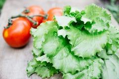 φρέσκα λαχανικά, ντομάτες, αγγούρια, μαρούλι σε έναν ξύλινο πίνακα στοκ εικόνα