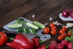 Φρέσκα λαχανικά που τεμαχίζονται για μια σαλάτα σε έναν τέμνοντα πίνακα Στοκ Εικόνα