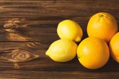 Φρέσκα λεμόνια και πορτοκάλια στον καφετή ξύλινο πίνακα Στοκ Εικόνα