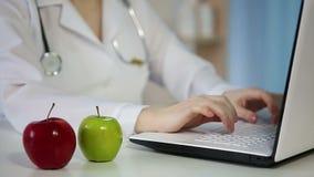 Φρέσκα μήλα στον πίνακα, θηλυκή εργασία γιατρών στην αρχή Σιτηρέσιο, υγιής τρόπος ζωής φιλμ μικρού μήκους