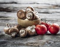 Φρέσκα μανιτάρια και ώριμες ντομάτες στο αυθεντικό ξύλο Στοκ εικόνα με δικαίωμα ελεύθερης χρήσης
