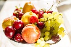 Φρέσκα μικτά φρούτα, μούρα στο κύπελλο Φρούτα αγάπης, μούρο Φως του ήλιου Στοκ Εικόνες