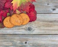 Φρέσκα μπισκότα μήλων καραμέλας και φύλλα φθινοπώρου στο αγροτικό ξύλινο β Στοκ εικόνα με δικαίωμα ελεύθερης χρήσης