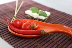 Φρέσκα ντομάτες και τσίλι κερασιών στο πιάτο Στοκ Εικόνα