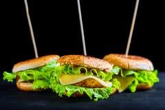 Φρέσκα νόστιμα τρία burgers στο μαύρο υπόβαθρο Στοκ εικόνα με δικαίωμα ελεύθερης χρήσης