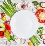 Φρέσκα οργανικά λαχανικά και συστατικά καρυκευμάτων για το νόστιμο χορτοφάγο μαγείρεμα γύρω από το κενό άσπρο πιάτο, τοπ άποψη Στοκ Εικόνες
