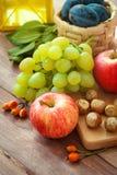 Φρέσκα οργανικά εποχιακά φρούτα, φρούτα φθινοπώρου, καρύδια - συγκομιδή φθινοπώρου στον αγροτικό πίνακα Στοκ Εικόνες