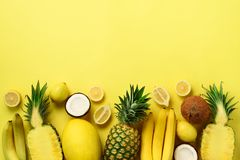 Φρέσκα οργανικά κίτρινα φρούτα πέρα από το ηλιόλουστο υπόβαθρο Μονοχρωματική έννοια με την μπανάνα, καρύδα, ανανάς, λεμόνι, πεπόν στοκ εικόνα με δικαίωμα ελεύθερης χρήσης