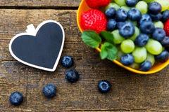 Φρέσκα οργανικά φρούτα στον ξύλινο πίνακα, μαύρη καρδιά Στοκ φωτογραφία με δικαίωμα ελεύθερης χρήσης