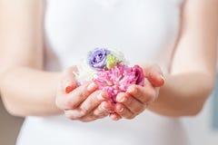 Φρέσκα λουλούδια στο χέρι γυναικών Έννοια της ομορφιάς και της SPA, υγειονομική περίθαλψη Στοκ Εικόνα