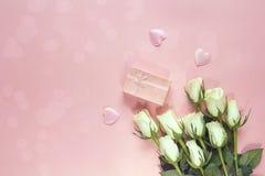 Φρέσκα λουλούδια τριαντάφυλλων με το κιβώτιο δώρων και καρδιές σε ένα ρόδινο backgroun Στοκ φωτογραφία με δικαίωμα ελεύθερης χρήσης
