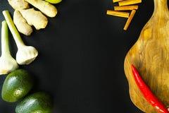 Φρέσκα πιπερόριζα, σκόρδο, αβοκάντο και καρυκεύματα στο μαύρο υπόβαθρο Στοκ Εικόνα