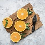 Φρέσκα πορτοκάλια περικοπών με τα φύλλα και μια ξύλινη συντριβή για τα φρούτα, στον αγροτικό ξύλινο δίσκο, τη τοπ άποψη Στοκ φωτογραφίες με δικαίωμα ελεύθερης χρήσης