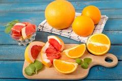 Φρέσκα πορτοκάλια και γκρέιπφρουτ στο ξύλινο υπόβαθρο Στοκ Εικόνες