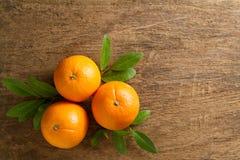 Φρέσκα πορτοκάλια με τα φύλλα στο ξύλινο υπόβαθρο Στοκ εικόνα με δικαίωμα ελεύθερης χρήσης