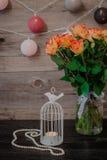 Φρέσκα πορτοκαλιά τριαντάφυλλα στο βάζο Λίγο άσπρο κηροπήγιο Στοκ Εικόνες