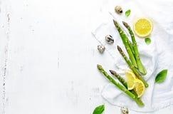 Φρέσκα πράσινα αυγά σπαραγγιού, λεμονιών και ορτυκιών στο άσπρο ξύλινο υπόβαθρο Συμβολική εικόνα r στοκ φωτογραφίες