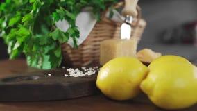 Φρέσκα πράσινα και λεμόνια στον πίνακα κουζινών, φρούτα και λαχανικά, που μαγειρεύουν από τη συνταγή, τρόφιμα για το μαγείρεμα φιλμ μικρού μήκους
