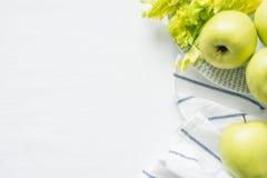 Φρέσκα πράσινα μήλα και σέλινο στο άσπρο υπόβαθρο υφασμάτων Στοκ Φωτογραφίες