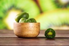 Φρέσκα πράσινα μίνι φρούτα ακτινίδιων μωρών με το τεμαχισμένο ακτινίδιο στοκ εικόνες