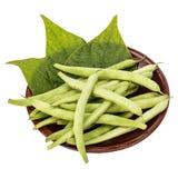 Φρέσκα πράσινα φασόλια και φύλλα σε ένα πιάτο αργίλου σε έναν πίνακα στοκ εικόνα με δικαίωμα ελεύθερης χρήσης