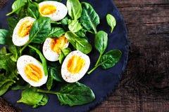Φρέσκα πράσινα φύλλα μωρών σπανακιού και βρασμένα αυγά που κόβονται σε ένα μισό επάνω Στοκ Φωτογραφίες
