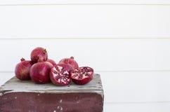 Φρέσκα ρόδια περικοπών στον ξεπερασμένο ξύλινο πίνακα, που απομονώνεται Στοκ φωτογραφία με δικαίωμα ελεύθερης χρήσης