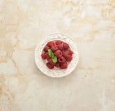 Φρέσκα σμέουρα σε ένα πιάτο σε ένα μαρμάρινο υπόβαθρο Στοκ Εικόνες