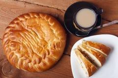 Φρέσκα σπιτικά πίτα και τσάι μήλων με το γάλα σε ένα ξύλινο υπόβαθρο Στοκ φωτογραφία με δικαίωμα ελεύθερης χρήσης