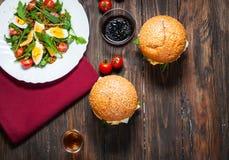 Φρέσκα σπιτικά burgers με ένα arugula και ένα οινόπνευμα σαλάτας στο σκοτεινό υπόβαθρο επάνω από την όψη Τοπ όψη Στοκ εικόνες με δικαίωμα ελεύθερης χρήσης