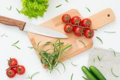 Φρέσκα συστατικά για την εύγευστη σαλάτα στον ξύλινο πίνακα έτοιμο για το μαγείρεμα Στοκ Εικόνες