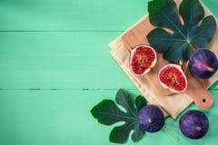 Φρέσκα σύκα με τα φύλλα στο πράσινο ξύλινο υπόβαθρο Στοκ Εικόνα