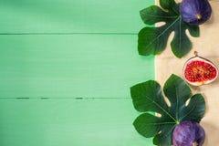 Φρέσκα σύκα με τα φύλλα στο πράσινο ξύλινο υπόβαθρο Στοκ Εικόνες