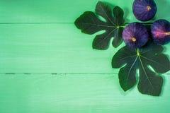 Φρέσκα σύκα με τα φύλλα στο πράσινο ξύλινο υπόβαθρο Στοκ φωτογραφίες με δικαίωμα ελεύθερης χρήσης