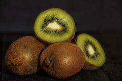 Φρέσκα σύνολο και μισά ακτινίδιων σε έναν μαύρο ξύλινο πίνακα Τα φρούτα ακτινίδιων είναι χρήσιμα Στοκ εικόνες με δικαίωμα ελεύθερης χρήσης
