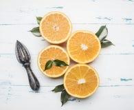 Φρέσκα τεμαχισμένα πορτοκάλια με τα φύλλα και ξύλινη συντριβή για τα φρούτα, αγροτικό ξύλινο υπόβαθρο, τοπ άποψη Στοκ Φωτογραφία
