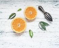 Φρέσκα τεμαχισμένα πορτοκάλια με τα φύλλα και ξύλινη συντριβή για τα φρούτα, αγροτικό ξύλινο υπόβαθρο, τοπ άποψη, διάστημα για το Στοκ εικόνες με δικαίωμα ελεύθερης χρήσης