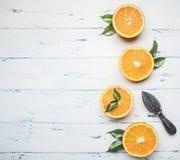 Φρέσκα τεμαχισμένα πορτοκάλια με τα φύλλα και ξύλινη συντριβή για τα φρούτα, στο αγροτικό ξύλινο υπόβαθρο, άποψη, διάστημα για το Στοκ φωτογραφία με δικαίωμα ελεύθερης χρήσης