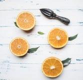 Φρέσκα τεμαχισμένα πορτοκάλια με τα φύλλα και ξύλινη συντριβή για τα φρούτα, αγροτικό ξύλινο υπόβαθρο, τοπ άποψη Στοκ Εικόνες